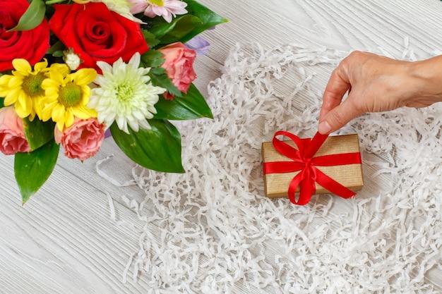 회색 나무 판자에 선물 상자가 있는 꽃다발과 여자의 손. 평면도.