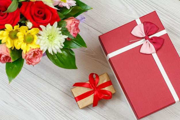 灰色の木の板に花とギフトボックスの花束。上面図。