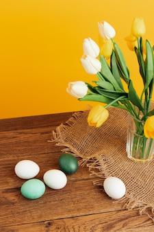 花の花束イースターエッグ休日の伝統黄色の背景。
