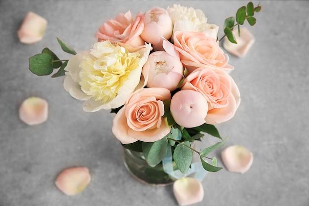 灰色のテーブルの上に花瓶の花の花束