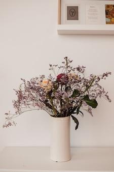 밝은 방에 있는 흰색 꽃병에 꽃다발