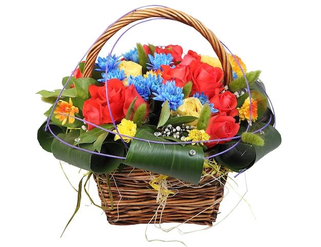 籐のかごの中の花の花束、赤と黄色のバラ、青い菊と白い背景で隔離の黄色のガーベラのフラワーアレンジメント。