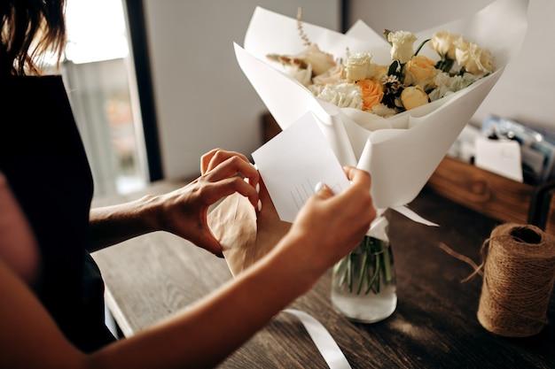 흰색 종이에 포장된 파스텔 색상의 꽃다발은 꽃병에 있습니다. 꽃집은 봉투에 엽서를 넣습니다.