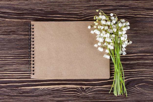 Букет цветов ландыша и пустой бумажный блокнот на коричневом деревянном деревенском столе сверху, вид сверху, место для текста, плоская планировка.