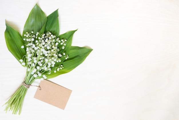 꽃 릴리 밸리 및 복사 공간 나무 테이블에 빈 종이 시트의 꽃다발.