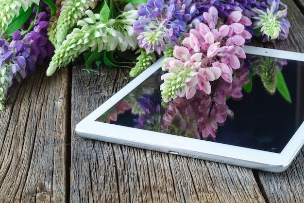 タブレットコンピューターと木製のテーブルの上に花の花束
