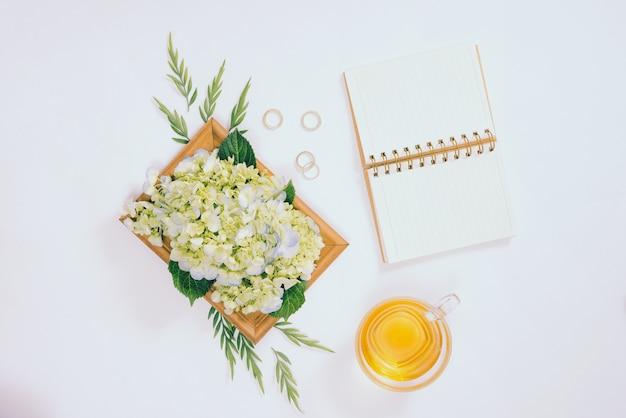 Букет цветов с пустой записной книжкой и стаканом чая