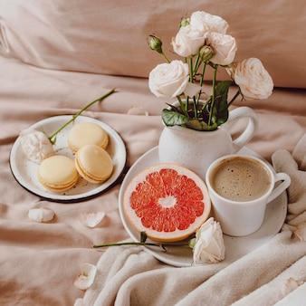 ベッドの上に朝のコーヒーとグレープフルーツと花の花束