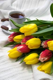 Букет цветов желтых и розовых тюльпанов на белой ткани с чашкой чая в фарфоровой чашке