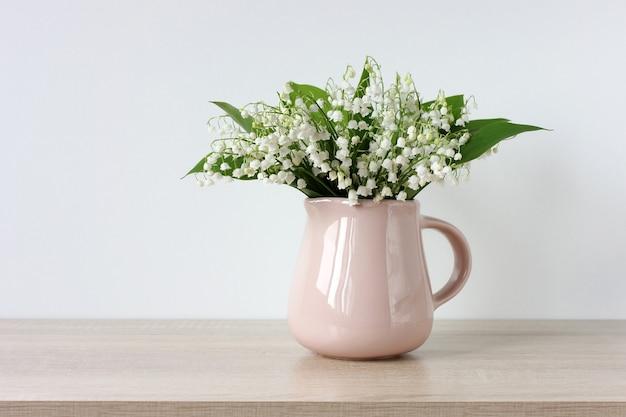 スズランの花束。明るい背景の水差しの花。