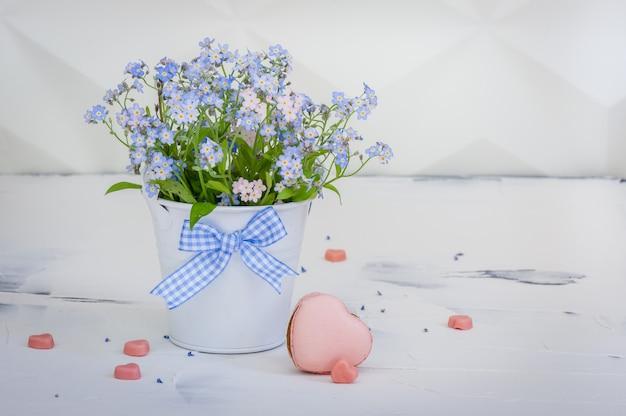 금속 양동이와 핑크 하트 모양의 마카롱에 물 망 초 꽃다발.