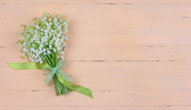 Букет душистых цветов ландыша с зелено-белым бантом в горошек на розовом деревянном фоне с копией пространства
