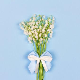 Букет из ароматных цветов ландыша с бело-синим бантом на синем фоне крупным планом, вид сверху