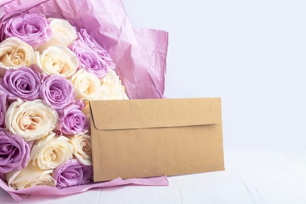新鮮な驚くべき白と紫のバラの花束とクラフト封筒。母の休日、バレンタインデー、誕生日、記念日、結婚式のギフト。ギフト包装conceptrテキスト。