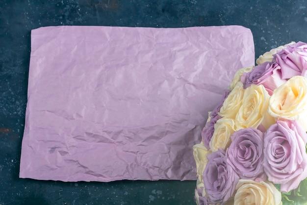 新鮮な驚くべき白と紫のバラと暗い背景にクラフト紙の花束。母、バレンタイン、誕生日、記念日、結婚式のテキストの休日のギフト。