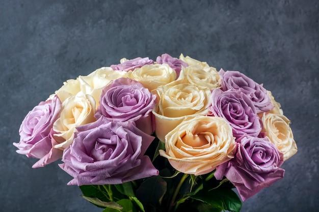 はがき、カバー、バナーの暗い背景にペーパークラフトで新鮮な驚くべき白と紫のバラの花束。母の日、誕生日、結婚式の贈り物として美しい花。コピースペース