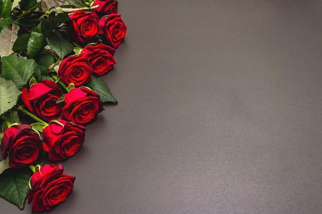 검은 돌 콘크리트 배경에 신선한 부르고뉴 장미 꽃다발. 향기로운 붉은 꽃, 발렌타인 데이, 결혼식 또는 생일 선물 개념