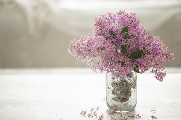 ガラスの花瓶に新鮮なライラックの花の花束