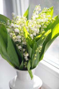 햇빛에 창턱에 신선한 은방울꽃 꽃의 꽃다발을 닫습니다.