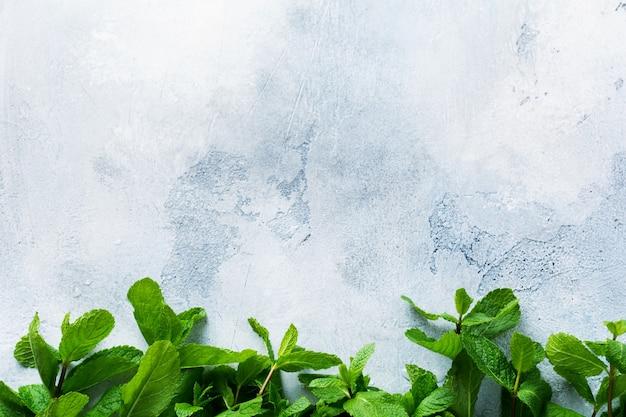 古い灰色のコンクリートのテーブルの上に横たわっている新鮮なミントの葉の花束。上面図。ゼロウェイストコンセプト。