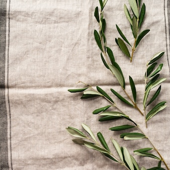 오래 된 빈티지 회색 냅킨 식탁보 테이블 배경에 신선한 올리브 나무 가지의 꽃다발. 천연 제품 개념. 평면도.
