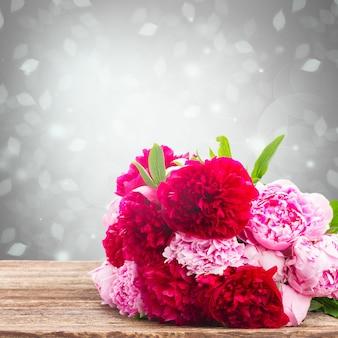 Букет из свежих розовых и красных пионов на деревянном столе