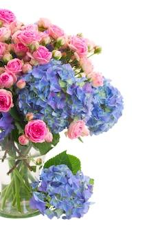 新鮮なピンクのバラと青いオルテンツィアの花の花束は、白いスペースで隔離のガラスの花瓶にクローズアップ
