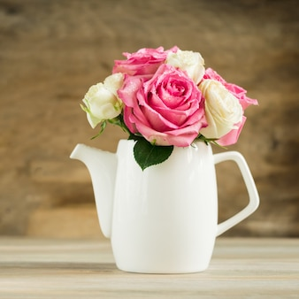 テーブルの上の白い水差しの新鮮なピンクのバラの花束