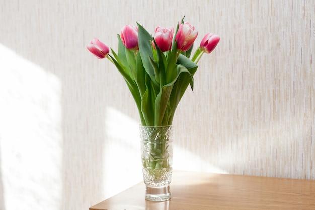 Букет свежих розовых тюльпанов в прозрачной вазе в залитой солнцем комнате