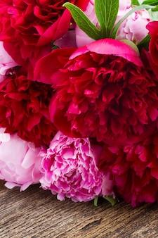 Букет из свежих красных и розовых пионов на деревянном столе