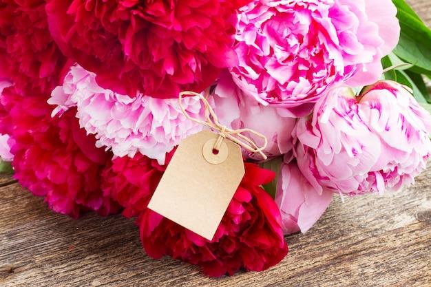 Букет из свежих красных и розовых пионов с пустой бумажной биркой на деревянном столе
