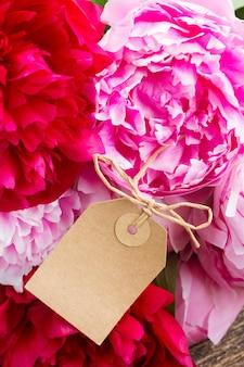 Букет из свежих красных и розовых пионов с пустой бумажной биркой