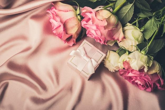 新鮮なバラの花束とシルク生地の背景にギフト