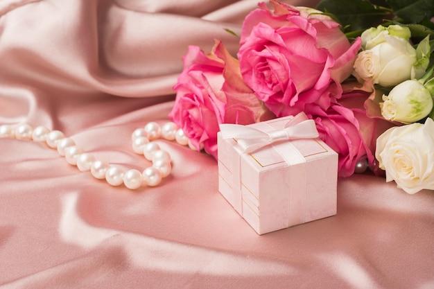 실크 직물의 배경에 신선한 장미 꽃다발과 선물
