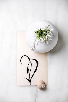 Букет из свежих весенних цветов подснежников в белой фарфоровой вазе с раковиной улитки и рисованной подснежник на белом мраморном столе. весенняя композиция