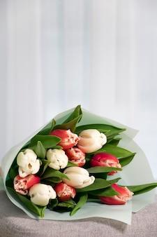 家の内部の房状の窓の近くの灰色のアームチェアに赤と白の新鮮なチューリップの花束