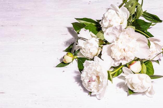 신선한 흰 모란 꽃다발입니다. 여름 섬세한 꽃, 낭만적인 선물 개념. 꽃꽂이, 트렌디한 하드 라이트, 어두운 그림자. 흰색 오래 된 널빤지 배경