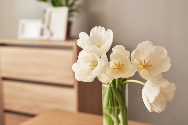 신선한 흰 튤립과 빈 사진 프레임의 꽃다발. 어머니의 날, 여성의 날, 3 월 8 일 봄 인사말 카드 템플릿.