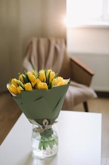 Букет свежих желтых тюльпанов на столе в интерьере гостиной