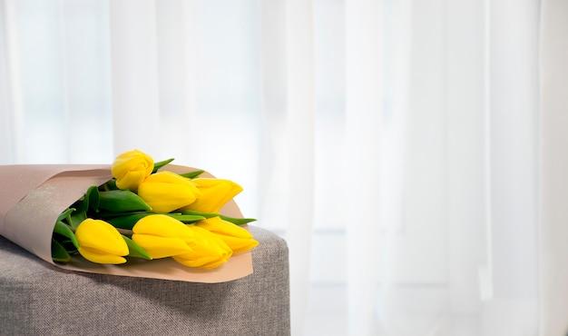 家の内部のチュール窓の近くの灰色のアームチェアに新鮮な黄色のチューリップの花束