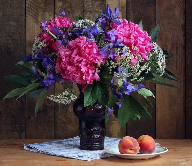 정원 꽃의 꽃다발 : 모란, 창포 및 복숭아 접시에. 소박한 아직도 인생.