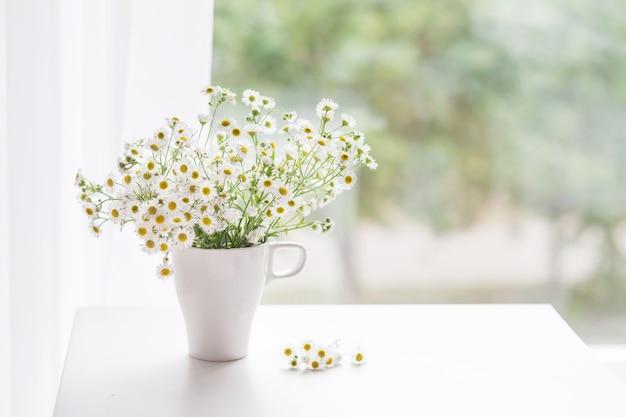 Букет из нежной ромашки в белой чашке. утренний свет в комнате. мягкий декор для дома, ваза с белыми цветами