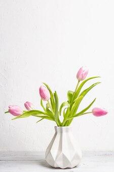 흰색 바탕에 세라믹 꽃병에 부드러운 핑크 튤립 꽃다발