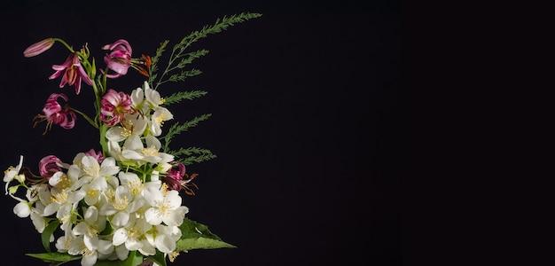 黒の背景にジャスミンの花の花束、コピースペースのカード