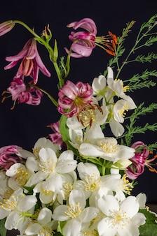 黒の背景に蘭とジャスミンの花の花束、カード
