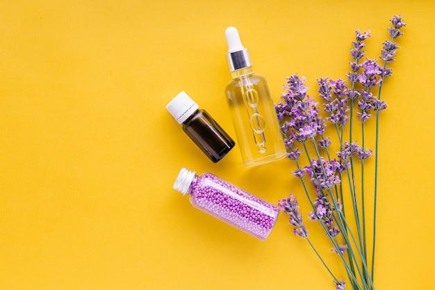 ラベンダーの花の花束とラベンダーのスキンケア化粧品のセット。ナチュラルスパ美容製品黄色の背景に新鮮なラベンダーの花のハーブ。ラベンダーエッセンシャルオイルセラムクリームバスビーズ。