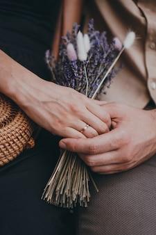 女の子の手でラベンダーの花の花束。手持ちの婚約指輪。手をつないでカップルが大好きです。愛、人間関係、旅行、恋愛の概念。