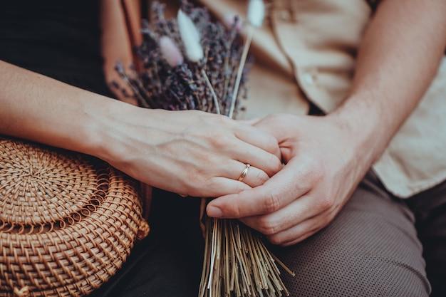 女の子の手でラベンダーの花の花束。手持ちの婚約指輪。手をつなぐ愛のカップル