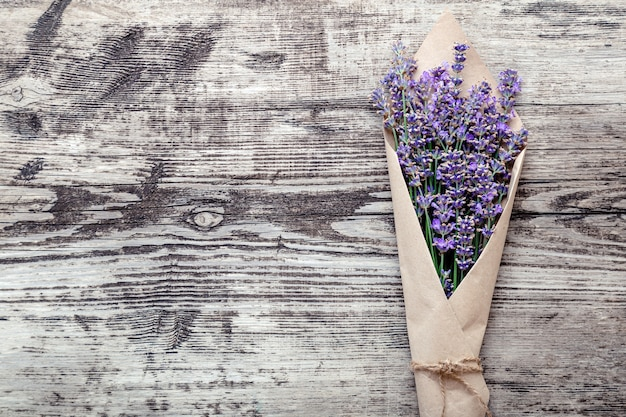 Букет лаванды в бумажной упаковке с копией места для текста. свежий букет цветов лаванды на старом деревенском деревянном столе. flatlay французский цветок в стиле прованс. ароматерапия с лавандой