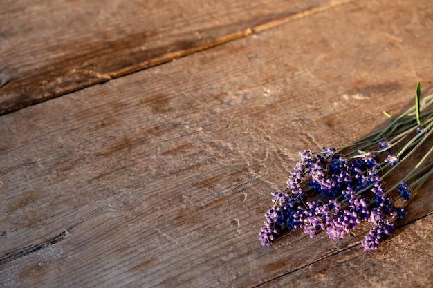 Букет веточек лаванды на коричневой деревянной стене. цветочная рамка или рамка с лавандой